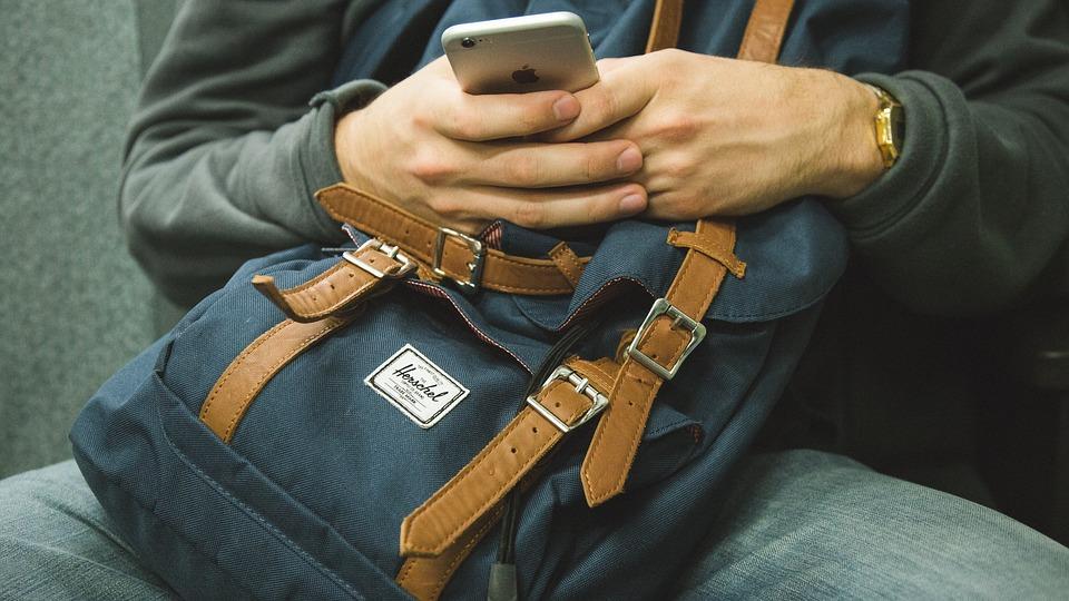 Człowiek z telefonem i plecakiem siedzący w Autobusie